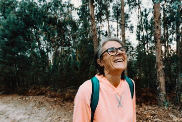 Old woman laughing in the middle of the forest in spain...