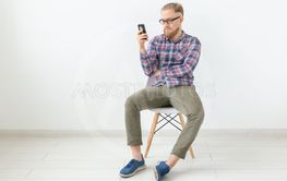 Young hipster bearded man sitting over the white...