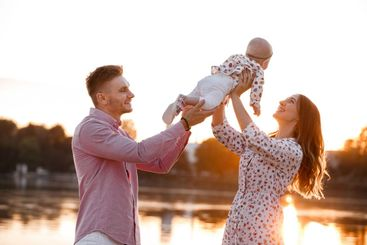 Beautiful woman lifts high her adorable baby girl up mid...