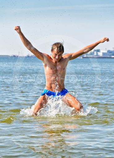 Semi nude handsome man jumping in the sea