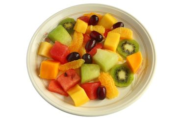 Healthy mixed fruit salad on a plate isolated over white.