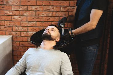In a barbershop, a man is washed his hair. Barber washes...
