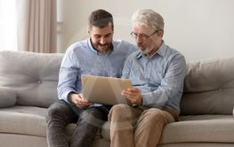Grown son and senior dad using laptop at home together