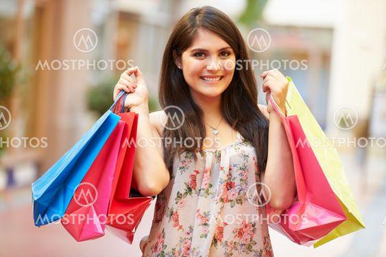 Woman Walking Through Mall Carrying Shopping Bags