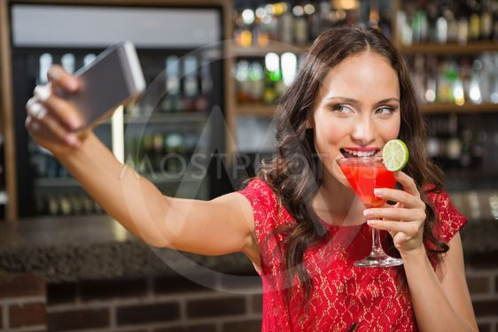 Pretty woman taking a selfie with her cocktail