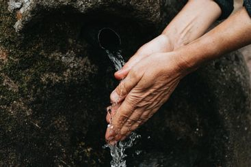 Old woman washing her hands close up of the hands in a...