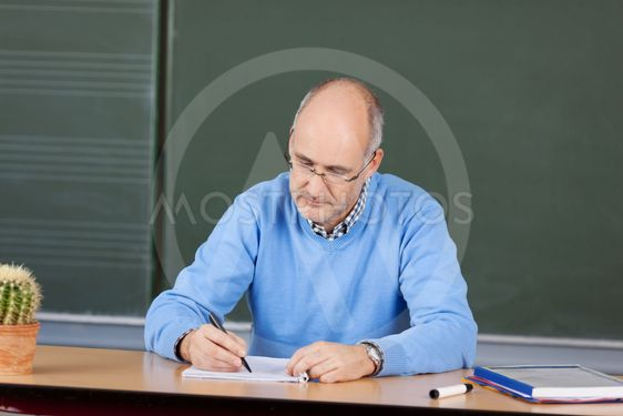 Teacher writing notes at his desk