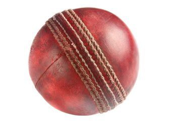 An old used red cricket ball, isolated on a white...