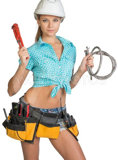 Pretty girl in helmet, shorts, shirt, tool belt with...
