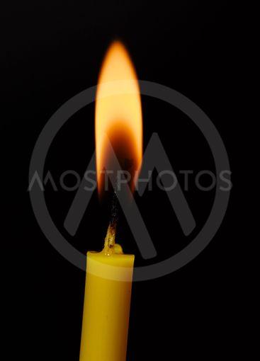 Burning candle on black background. Candle light. The...