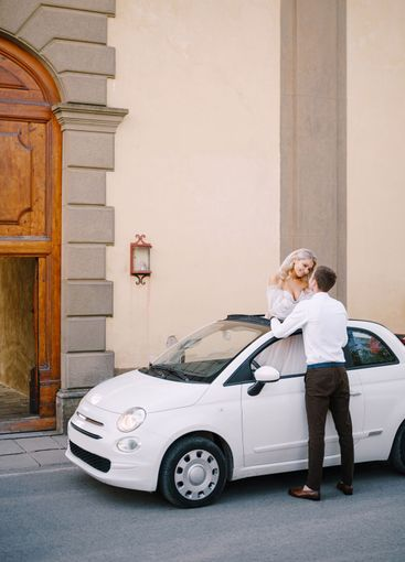 Beautiful bride standing up in a convertible and holding...