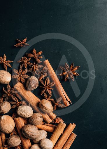 top view of carnation, cinnamon sticks and nutmegs on table