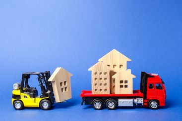 A yellow forklift loads a house figures on a red truck....