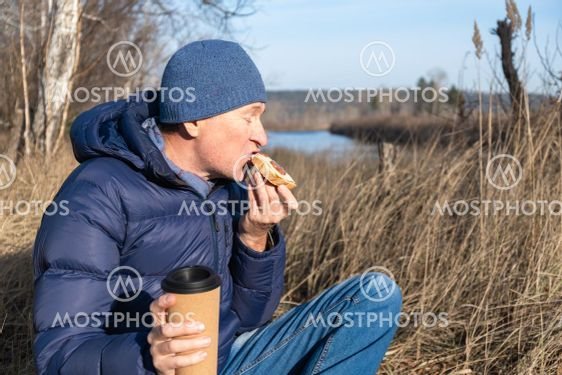 A man sits on the grass in the fall and eats a cheese...