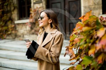 Modern woman using mobile phone at autumn outdoor