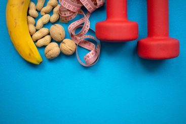 Banana, nuts, measuring tape and red dumbbells