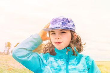Porträtt, ung tonårsflicka med keps i blåsigt väder.