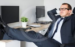 young businessman relaxing with legs on the table