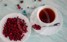 Cup of tea, cranberries on the plate
