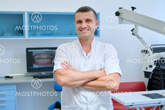 Portrait of confident friendly male dentist with crossed...