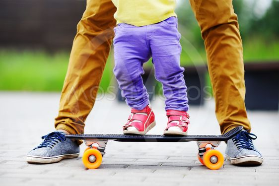 Toddler girl learning to skateboard with her father