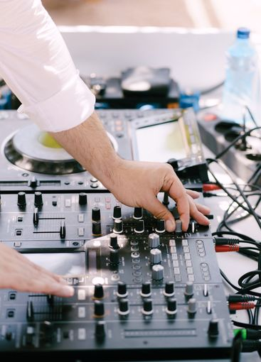 DJ plays music on the beach. Dj mixing beach party in...
