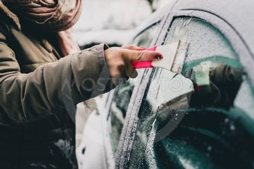 Cleaning a frosty window on a car.