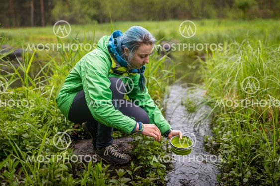 the girl washes tourist dishes by the river at the campsite