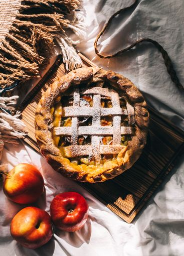Homemade apple pie on a wooden board with cinnamon and a...