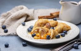 Crepes with apple filling, blueberry and caramel sauce.