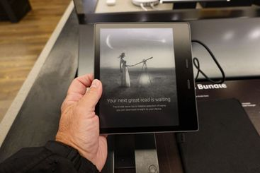 A person holding an  Amazon Kindle Oasis device that is...
