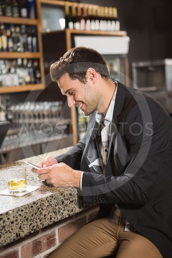 Handsome man having a whiskey and using smartphone