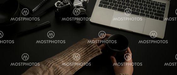 Female hands holding coffee mug on dark office desk with...