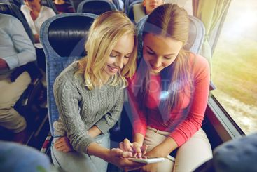 happy young women in travel bus with smartphone