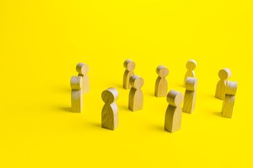 Figures of people stand randomly on a yellow background....
