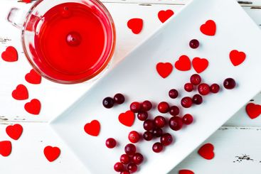Selective focus on cranberries and red hearts on a white...