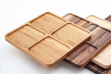Shaped wooden trays in row on white background
