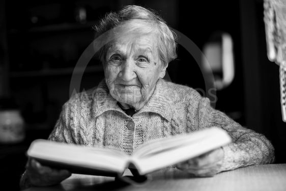 Elderly woman sitting at a table reading a book....