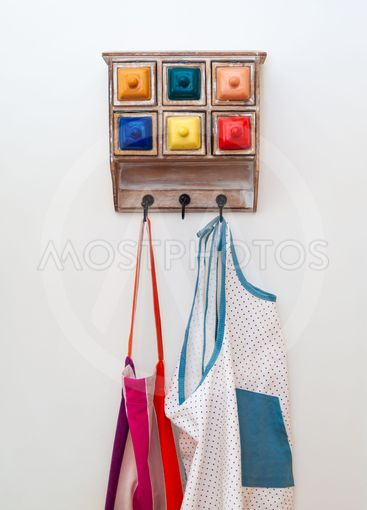 Kitchen aprons on colourful hanger with little drawers.