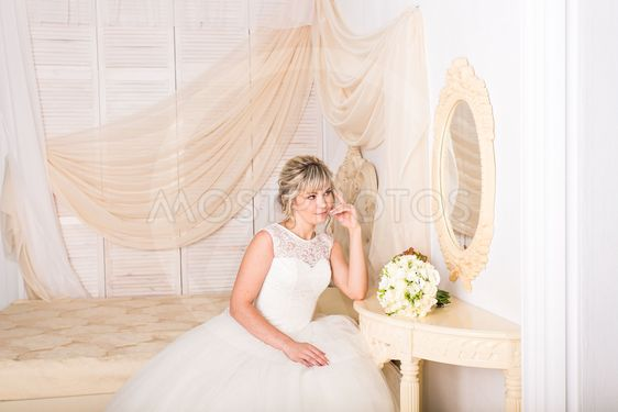 portrait of happy young woman in white wedding dress and...