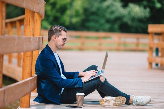 Young man with laptop working outdoors