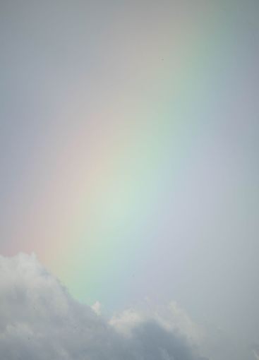 closeup of a beautiful rainbow full of color among clouds