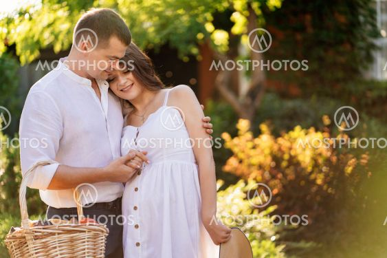 couple waiting baby walks in garden with basket