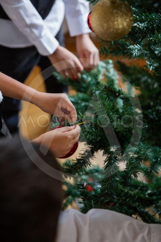 Barn hänger upp julgranskulor
