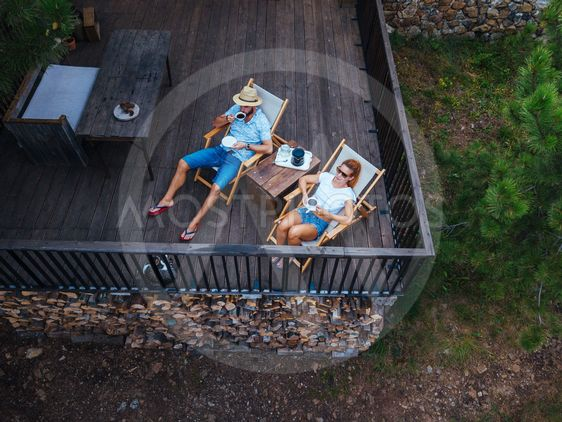 Young couple drinking coffee on terrace, aerial view