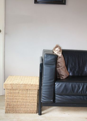 Interior design: Black leather sofa and wicker footstool