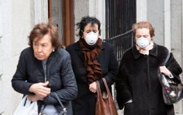 Women wearing protective face masks to prevent the...