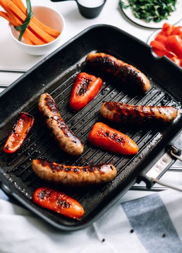 Sausages and bell peppers in a grill pan with vegetables