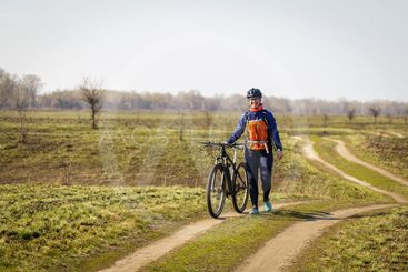 woman cyclist in the field leads the bike in his hands