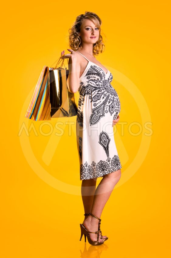 Lovely pregnant woman holding shopping bags isolated on...
